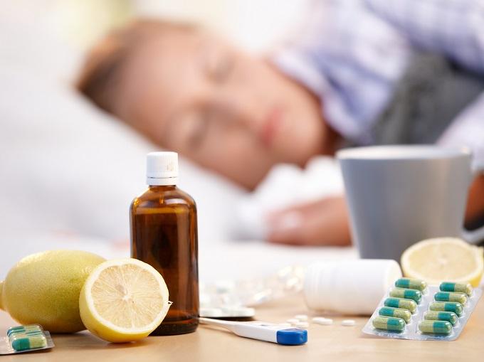 横になっている女性と、机の上の薬とレモン