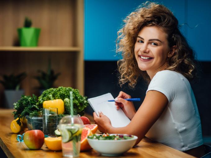 食事の内容をノートに記入する女性