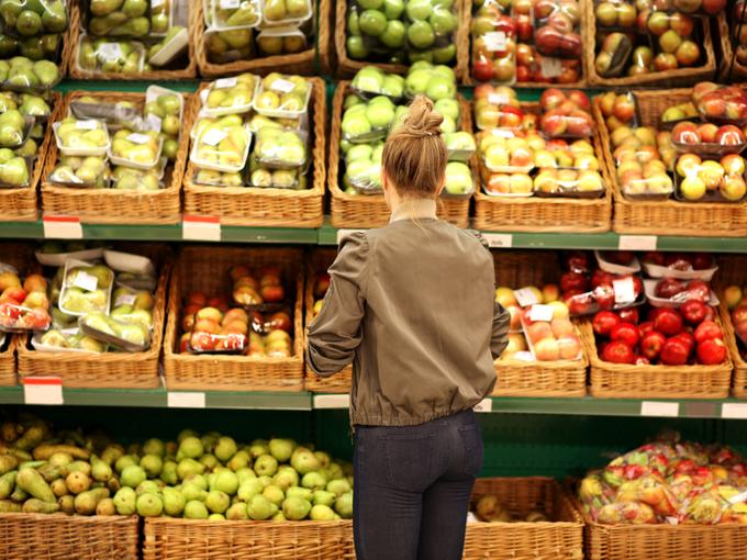 スーパーの野菜売り場に立つ女性