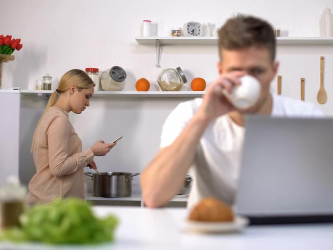 食事をしながらパソコンを見る男性と、調理しながらスマホを見る女性