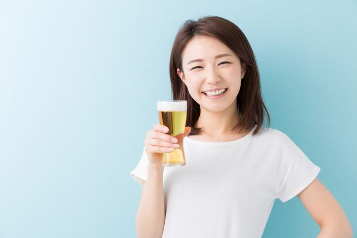 ビールを持って微笑む女性の画像