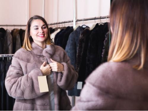 コートを試着する女性