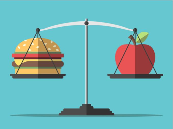 天秤にのったハンバーガーとりんご