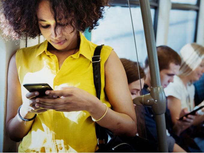 電車のなかでスマートフォンを見る女性