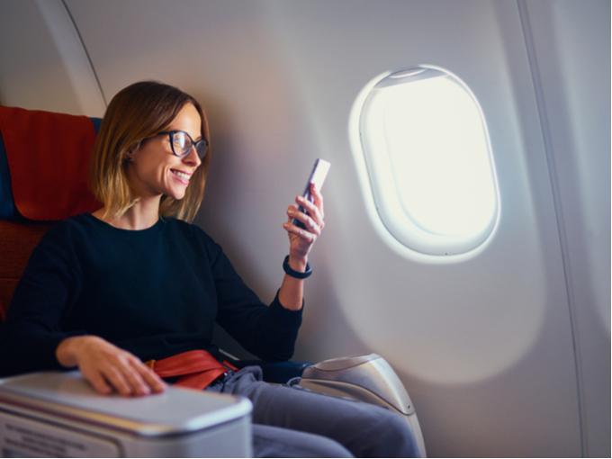 機内でスマホを見る女性