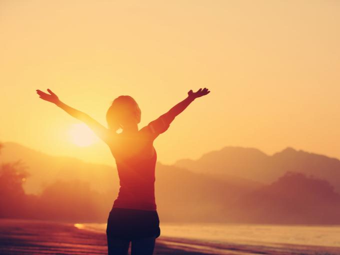 朝日に向かって両手を広げ喜びを表す女性