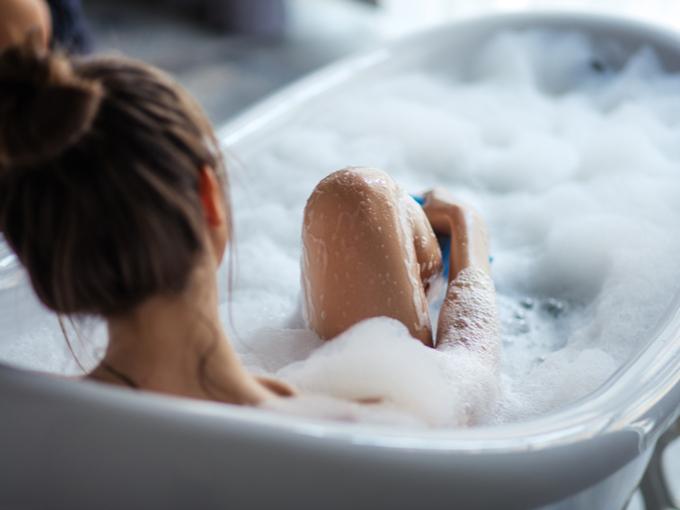 浴槽でセルフマッサージをする女性