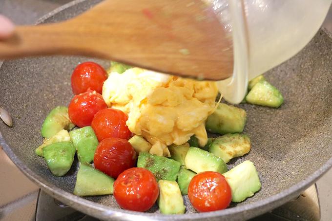 ミニトマトとアボカドを炒めるたフライパンに卵を戻し入れる