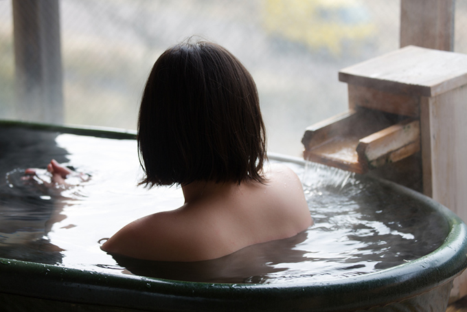 温泉で体を休めている女性