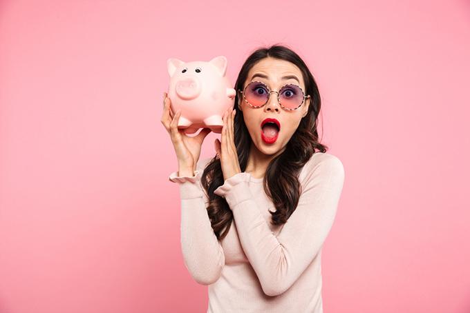 ブタの貯金箱を持っている女性の画像