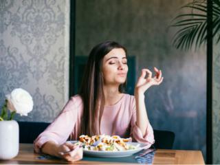 おいしそうに食事を食べる女性