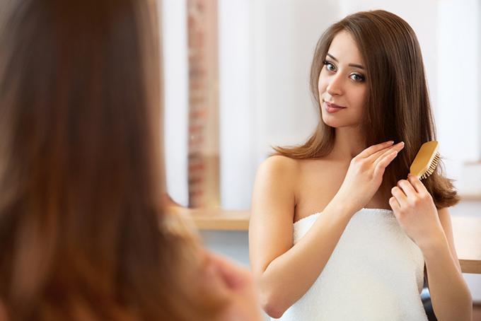 女性が髪の毛をとかしているイメージ画像
