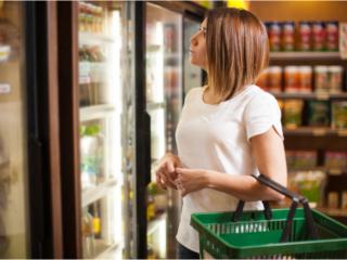コンビニの棚で商品を選ぶ女性