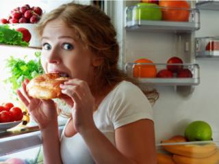 冷蔵庫の食材を口にする女性