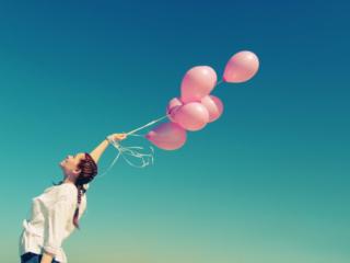 風船をもって空を仰ぐ女性