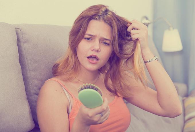 髪の毛をつかんで気分を落としている女性イメージ画像
