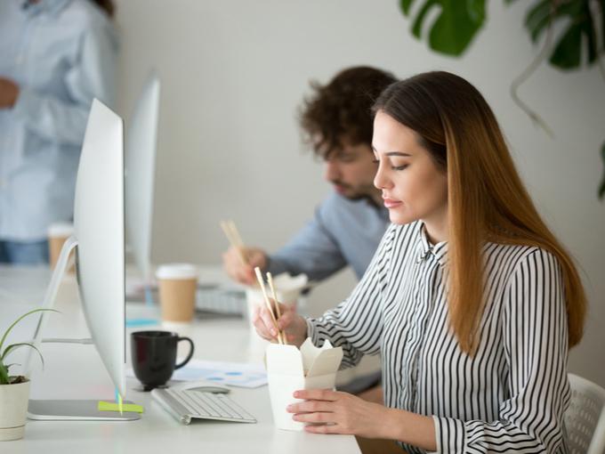職場のデスクで昼食をとる女性