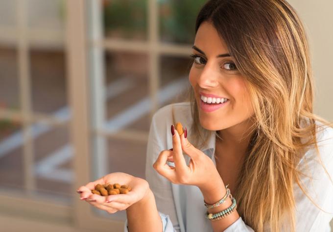 アーモンドを食べる女性画像