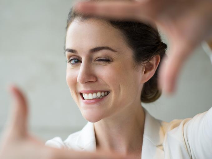 手でフレームをつくり、笑顔を見せる女性