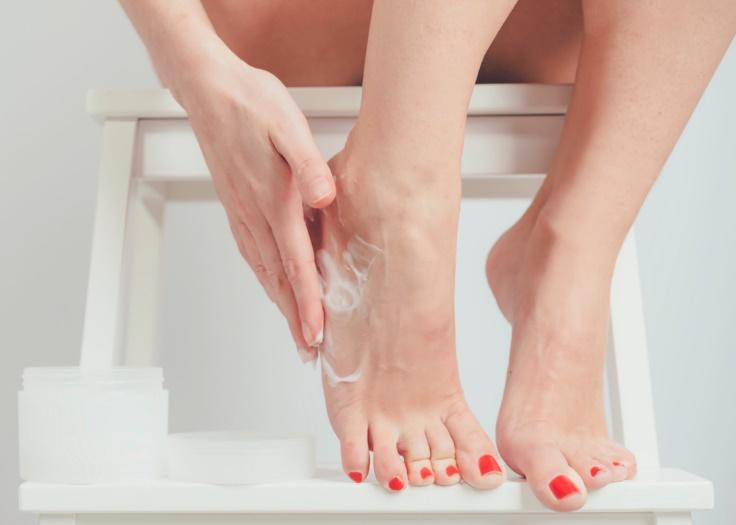 お風呂の椅子に座って、足にクリームを塗っている