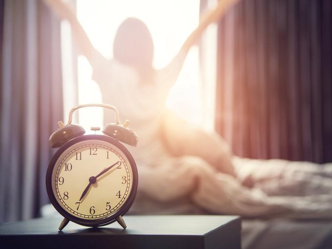 スッキリと目覚め、朝日を浴びる女性