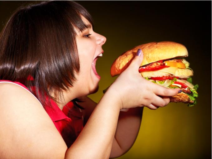 大きなハンバーガーにかぶりつく女性