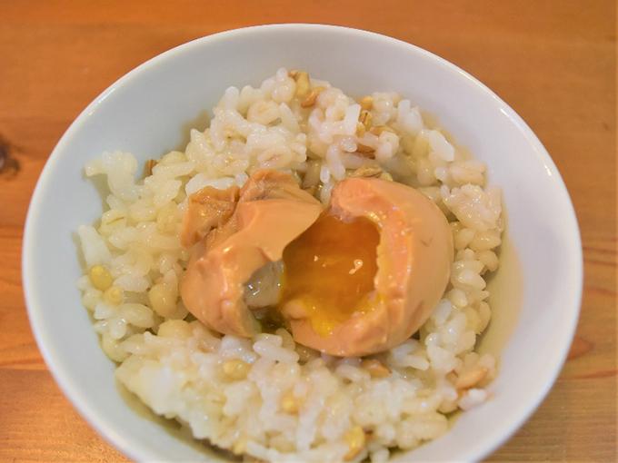 ご飯に乗せた半熟煮卵の画像