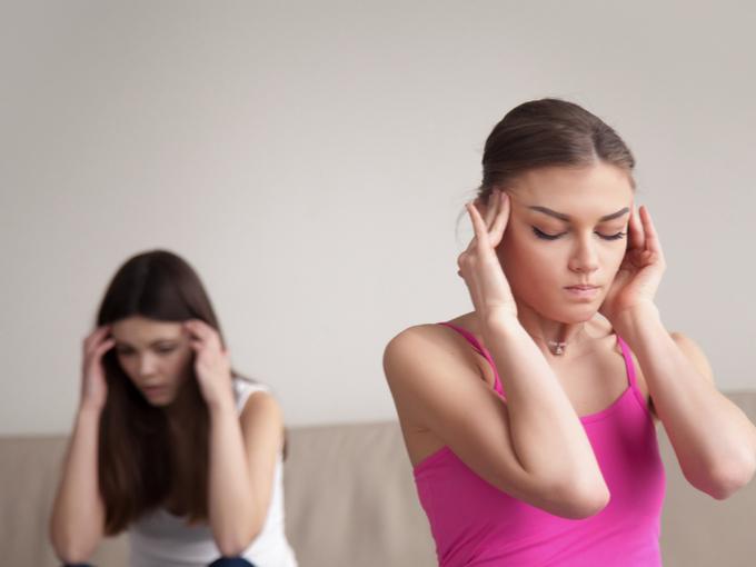 片頭痛でこめかみを抑える女性