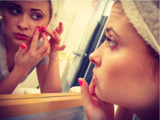 鏡で顔のたるみをチェックする女性