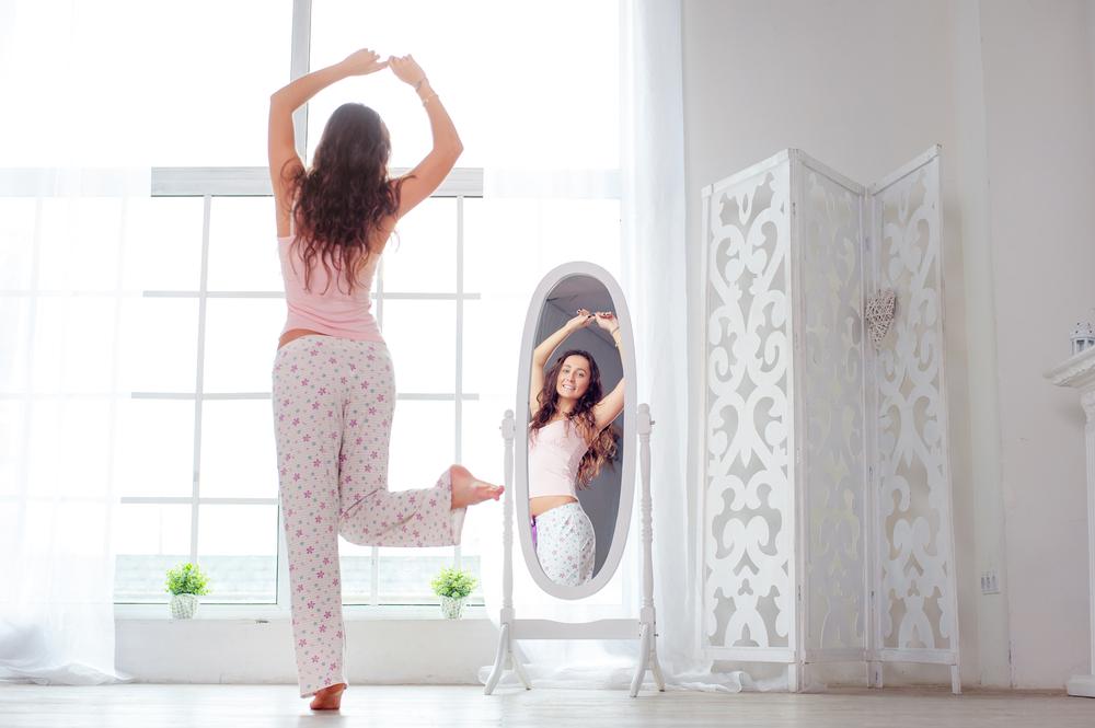 鏡の前でスタイルをたしかめている女性