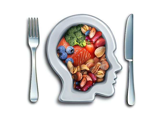 人間の頭部の形をしたお皿に野菜や魚などの食材が盛られているイメージカット