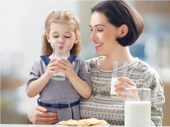 おやつと一緒に牛乳を飲む親子