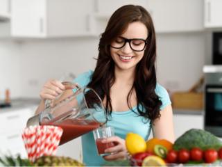 野菜ジュースを作ってコップに注ぐ女性
