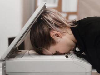 コピー機に顔をつけて寝る女性