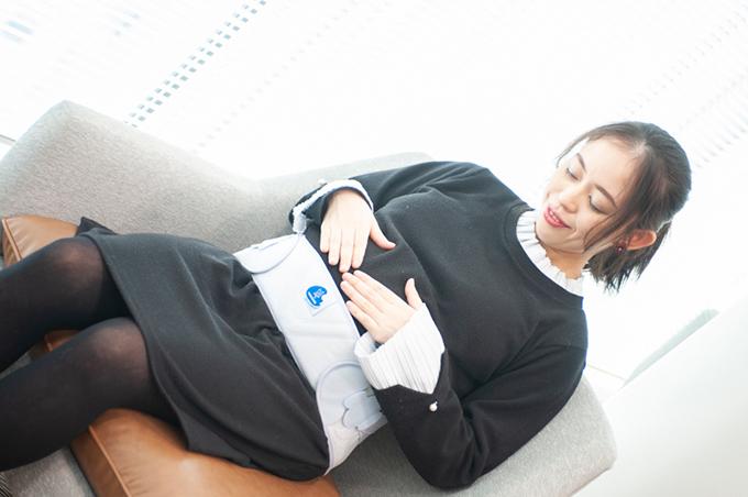 大きなおなかを支えるチュアンヌのサポーターをして座る平井さん