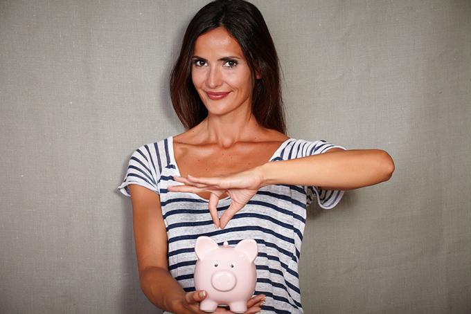 貯金箱にお金を入れている女性の画像