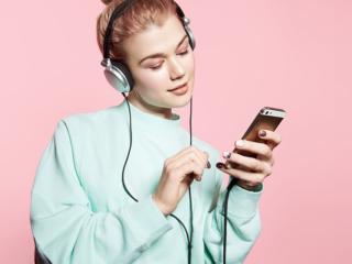 ヘッドホンで音楽を楽しんでいる女性の画像