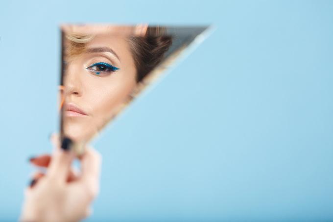 手鏡で顔をチェックする女性の画像