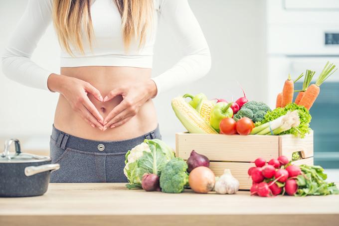 机の上にたくさんの野菜とお腹に手を当てている女性のイメージ画像