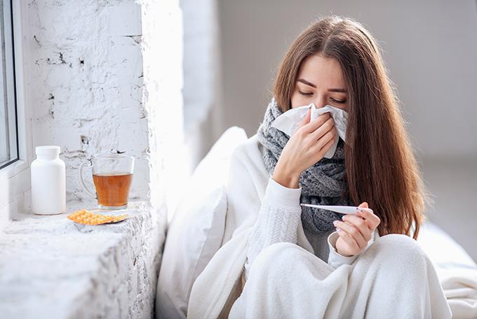体温を計っている風邪ぎみの女性