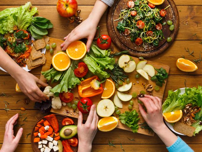 野菜やフルーツなどヘルシーな食材を食べる人たちの手