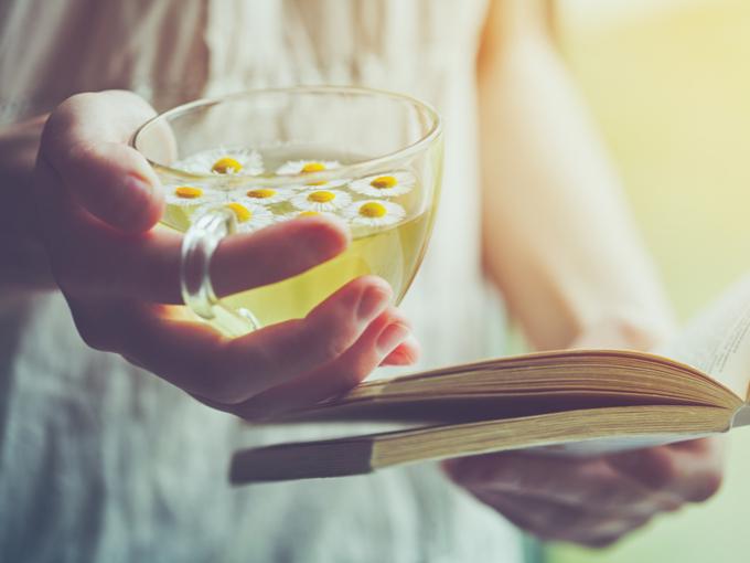 お茶を手に本を読んでいる様子