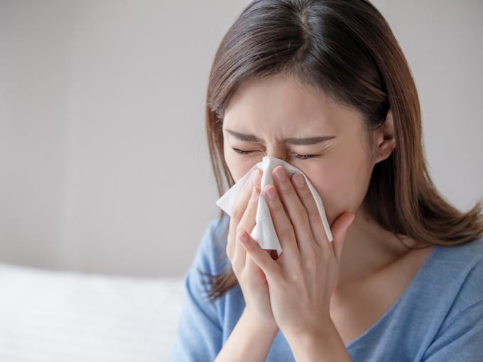 鼻をかむ花粉症の女性