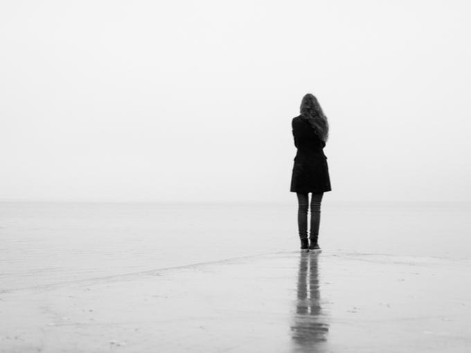 ひとりで海岸に立たずむ女性