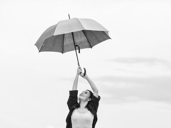 傘を広げ、空を見上げる女性