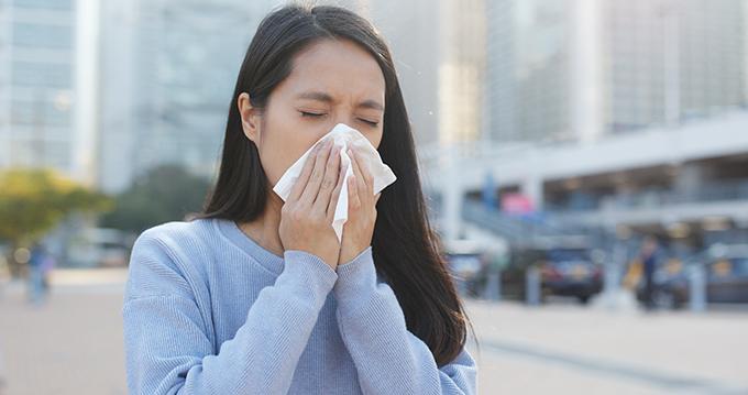 街中で鼻をかむ女性