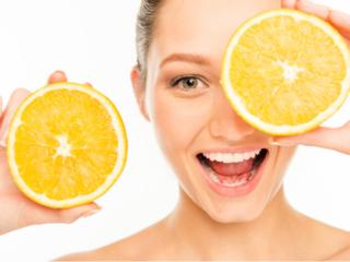 グレープフルーツを顔の前に掲げる女性