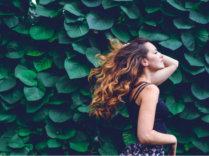 緑の植物が多い茂る横を歩く女性