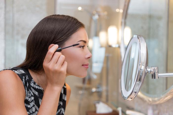 鏡を見ながらマスカラをつけている女性の画像