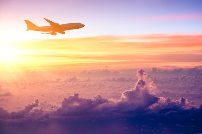 日の出、雲の上を飛ぶ飛行機